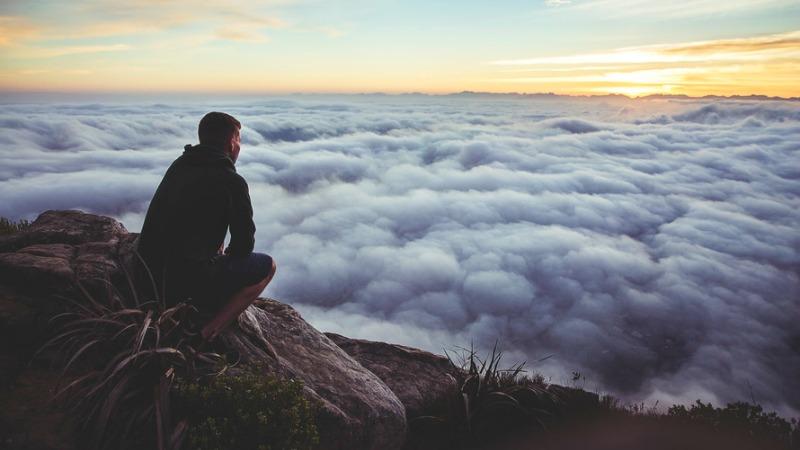 Человек любуется облаками с вершины горы