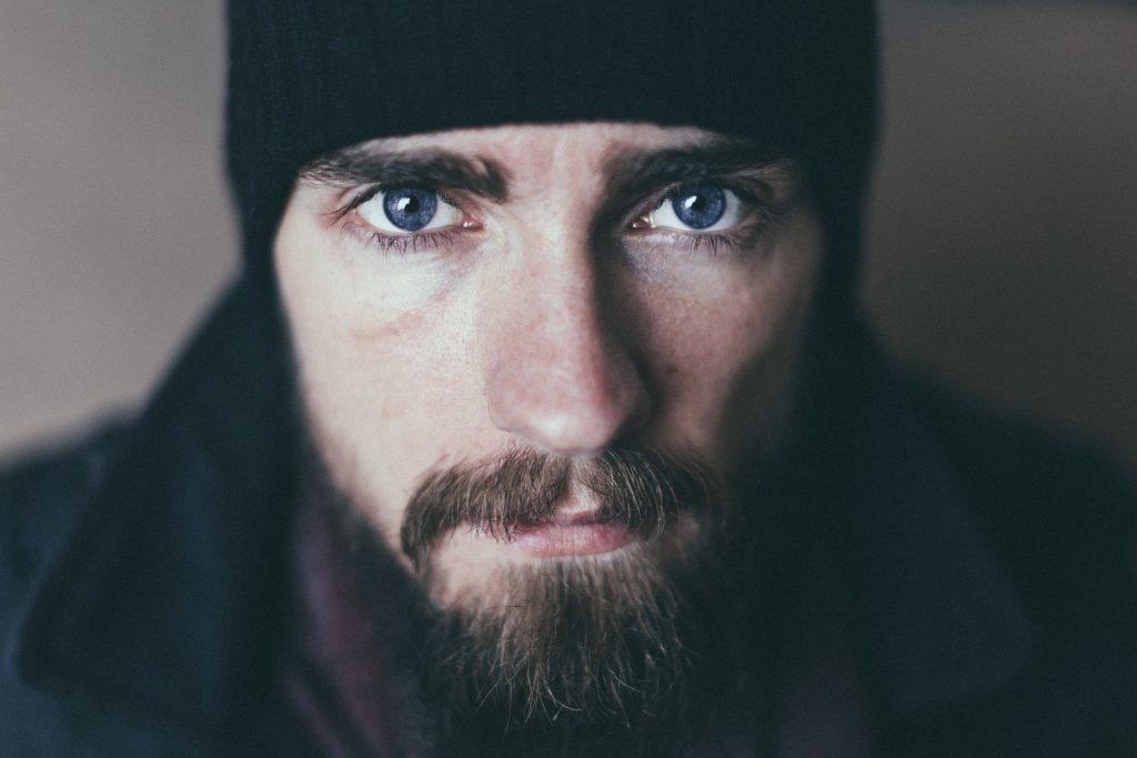 Бородатый мужчина в черной шапке, испытания