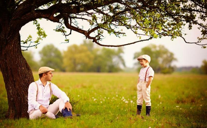 Отец и сын на поляне под деревом