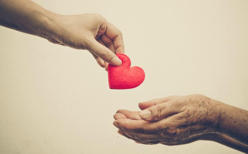 Бумажное сердце передается из рук в руки, сострадание