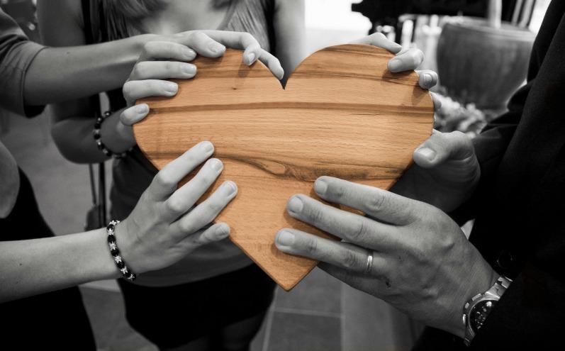 Руки держат деревянное сердце
