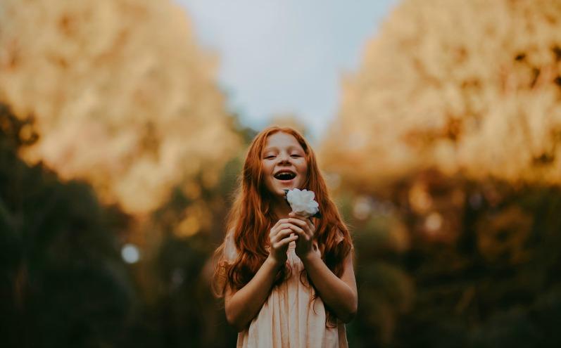 Рыжеволосая девочка с белым цветком улыбается