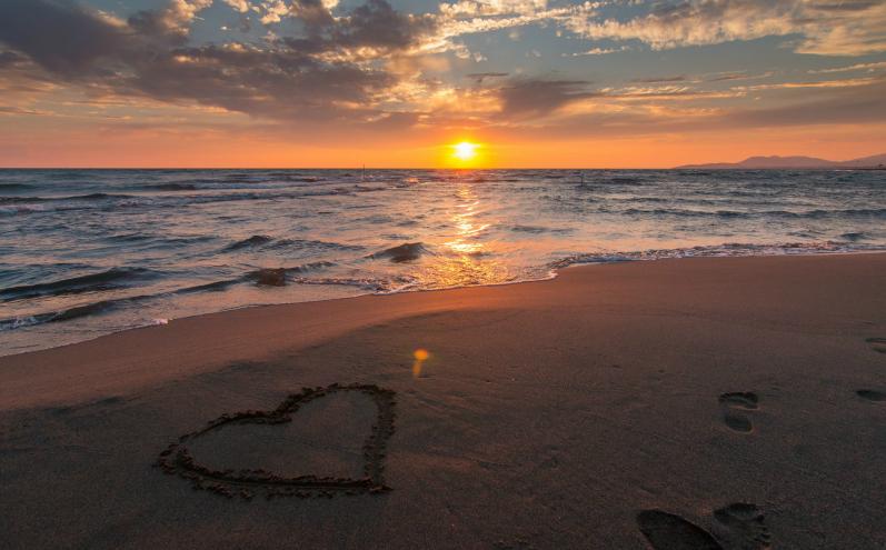 Нарисованное на песке сердце, следы на песке, пляж