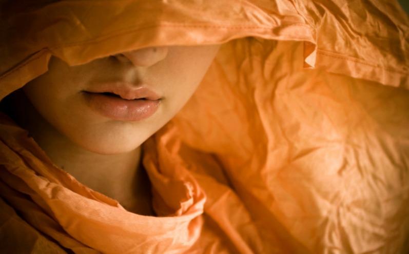 Лицо женщины, скрытое оранжевым капюшоном