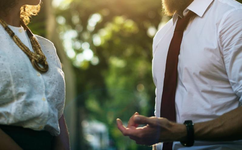 Мужчина в белой рубашке и женщина разговаривают