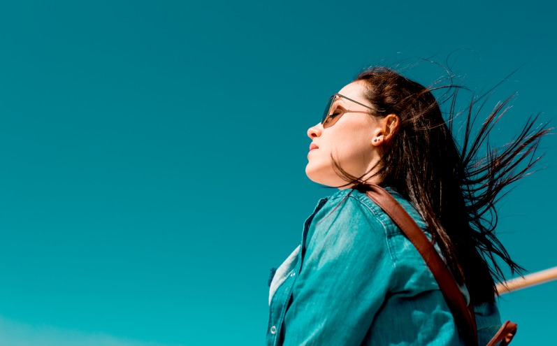 Девушка с развивающимися волосами на фоне ярко голубого неба