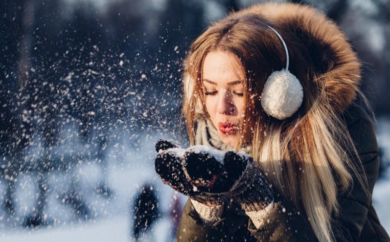 Девушка дует на снежинки