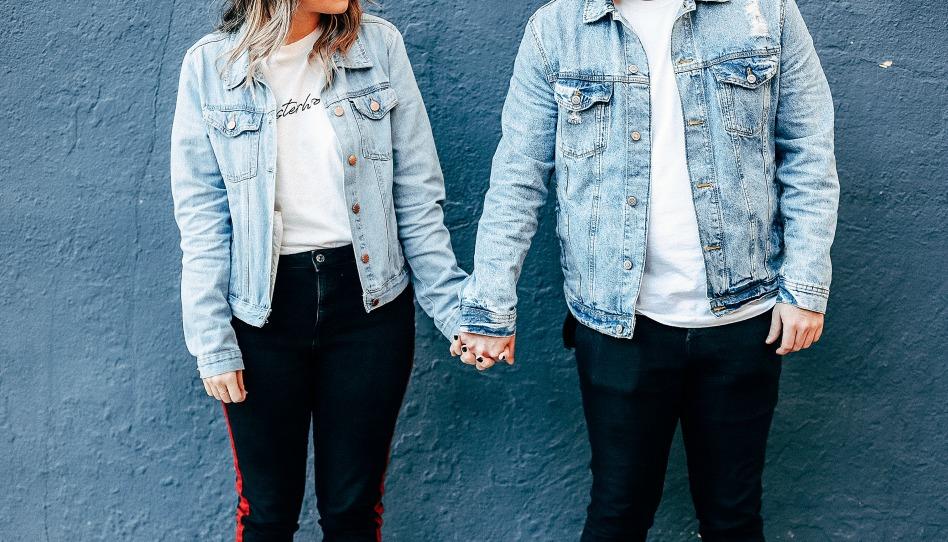 Парень и девушка в джинсовых куртках держатся за руки
